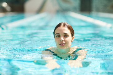 Pretty young woman swimming in pool and looking at camera while spending day in spa center