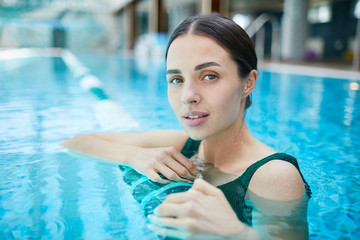 Young woman relaxing in water of swimming-pool at luxurious spa resort