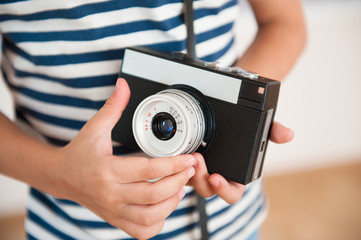closeup of kid wearing striped shirt with hands holding vintage camera