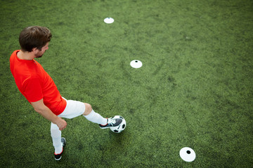 Young footballer keeping his foot on soccerball while standing by dividing line on green field