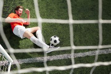 Top view of young goalkeeper catching soccer ball by leg while lying on green field by gates