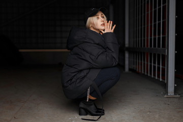 Young beautiful woman in fashion winter jacket and black stylish cap with fashionable pants with boots on a dark background