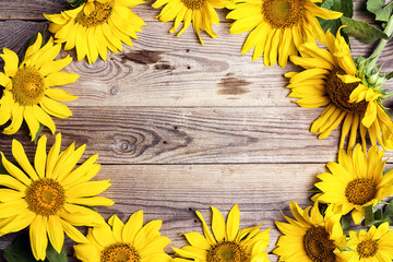 Frame of yellow sunflowers on a old wooden backgrounds. Space for text.