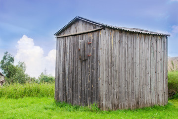 Rural landscape. Old-fashioned large barn with weathered walls in a green grass. On the edge of the village in the countryside. On the bright blue sky background.