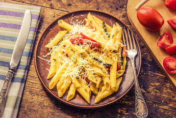 Classic Italian pasta with zucchini and tomatoes in a clay plate on a rustic table - top view