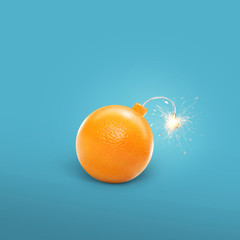 Concept of an orange bomb. Creative bomb with sparks. Juicy Orange