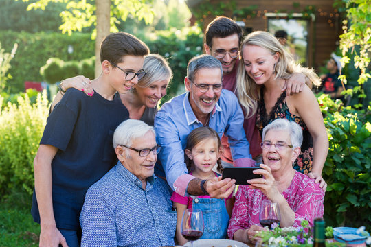 During a bbq, the family have fun sharing a video on a phone