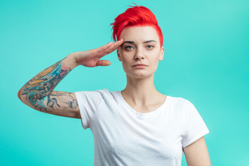 stylish woman with pink hair and tattoo doing a military. young awesome woman standing like a soldier isolated on the blue background