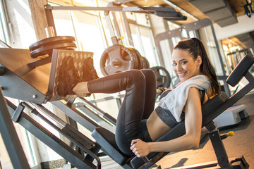 Beautiful woman sporty girl exercising using leg press machine at the gym