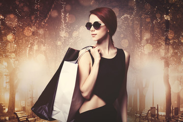 Style woman in sunglasses and black dress holding a shopping bags on city street at night. Bokeh on background