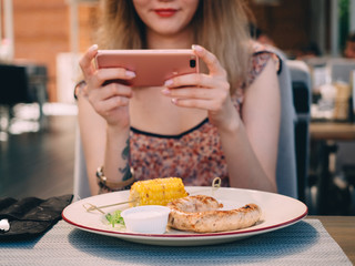 Young pretty girl in cafe taking photo of food