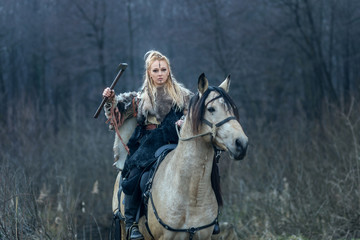 Blonde warrior viking woman riding horse with ax in hand against forest background ready to attack.