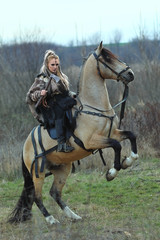 Blonde young Viking warrior woman riding a horse with ax in hand. Scandinavian warrior woman in forest with war makeup, ready to attack