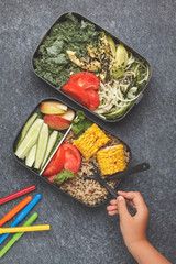 Healthy meal prep containers with quinoa, avocado, corn, zucchini noodles and kale. Child is eating at school from lunch box.