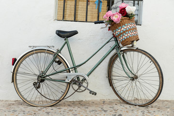 Vintage bicycle parked with basket of beautiful flowers. Old bike on the street leaning on the perimeter with window