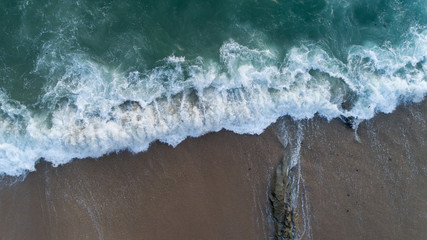 Aerial view drone shot of seascape scenic off beach in phuket thailand with wave crashing on the rocks.