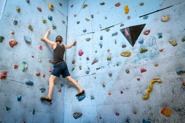 Teenage Boy Training Climbing On Indoor Climbing Wall