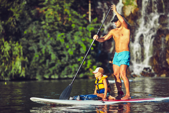 positive smiling boy in rashguard and his young father enjoying stand up paddleboarding