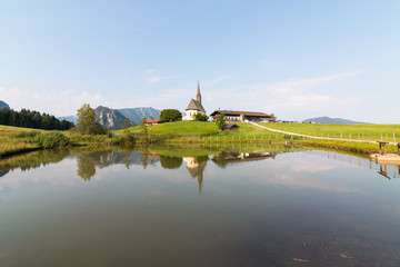 Inzell, Germany - August 5, 2018: View of the Nikolauskirche church in the Bavarian community of Inzell with the Alps in the background.