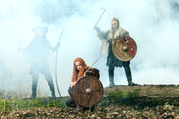 Warrior women with axes, shield and bows getting ready to attack. Vikings women getting ready to fight.