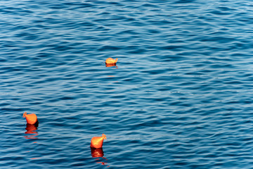 Three Orange Mooring Buoys on the Sea