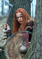 Redhead northern warrior woman with ax and shield hiding behind trees getting ready to attack