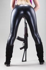 Beautiful female sexy ass with machine gun on gray background. Studio shooting