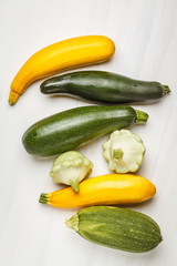 Different kinds of zucchini on white background, top view, copy space. Healthy clean eating concept.