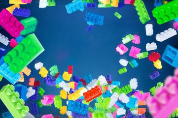 Pile of colored toy bricks falling on dark blue background. Studio shooting. High speed freezing photo