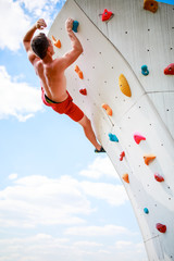 Photo from back of sportive man exercising on wall for climbing against cloudy sky