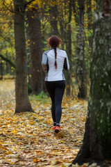 Photo from back of young brunette woman running through autumn park