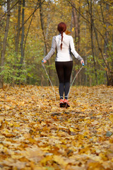 Photo from back of athlete woman jumping with rope at autumn forest