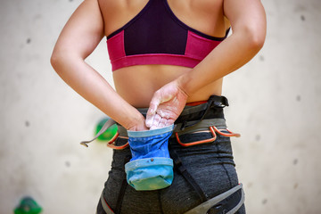 Photo from back of female athlete with bag of talc against background of wall for rock climbing