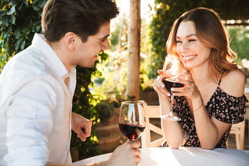 Loving couple sitting in cafe by dating drinking wine