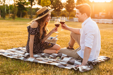 Loving couple sitting by dating drinking wine.
