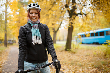 Smiling woman in helmet on bicycle against background of blue tram