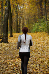 Image from back in full growth of girl running along autumn foliage
