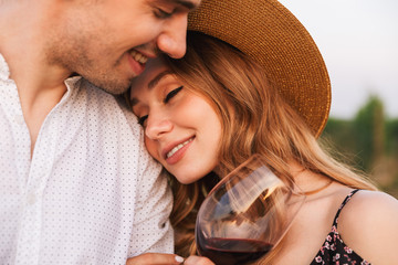 Loving couple outdoors holding glasses of wine.