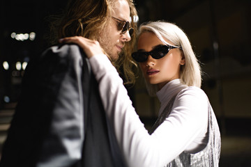 young stylish couple in sunglasses embracing on street at night