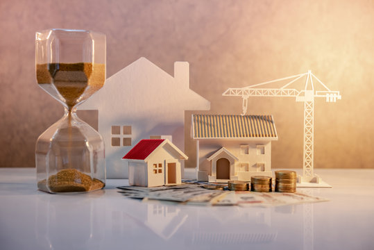 Real estate or property development. Construction business investment concept. Home mortgage loan rate. Coin stack on international banknotes with hourglasses, house and crane models on the table.