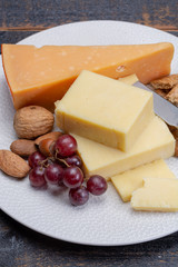 Aged English cheddar and old Dutch cheese, the most popular type of hard cheeses made from cow milk served as a dessert with nuts and grapes