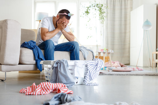 Tired young father overwhelmed with household chores