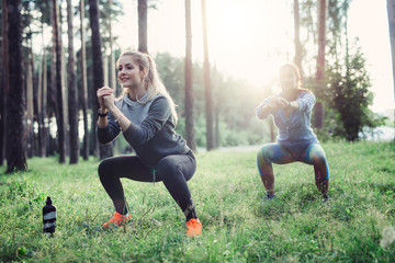 Fit young Caucasian women wearing jumpsuits working out in the forest doing squats in the early morning