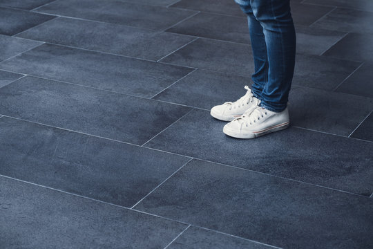 Close up woman standing on dark grey tile floor wear white sneaker canvas shoe.