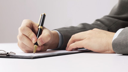 closeup.businessman signing a contract sitting at his Desk
