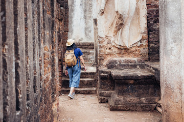 Asian tourist woman sightseeing in ancient of temple thai architecture at Sukhothai,Thailand. Female traveler in casual thai cloths style visiting city concept.