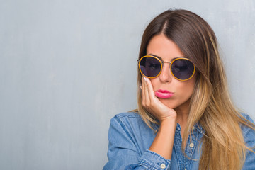 Young adult woman over grunge grey wall wearing retro sunglasses thinking looking tired and bored with depression problems with crossed arms.
