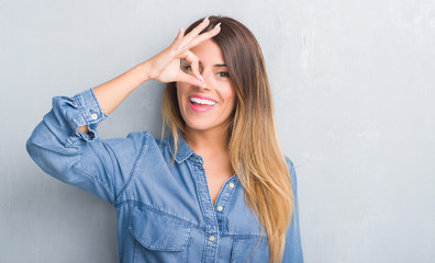Young adult woman over grey grunge wall wearing denim outfit with happy face smiling doing ok sign with hand on eye looking through fingers