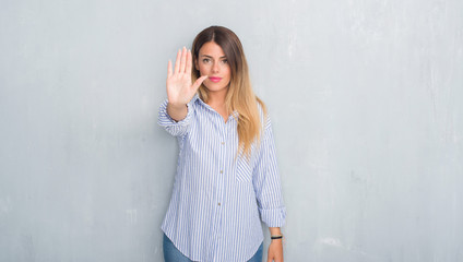 Young adult woman over grey grunge wall wearing fashion business outfit doing stop sing with palm of the hand. Warning expression with negative and serious gesture on the face.