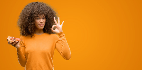 African american woman with a pizza slice doing ok sign with fingers, excellent symbol